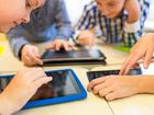 close up of school kids playing with tablet pc