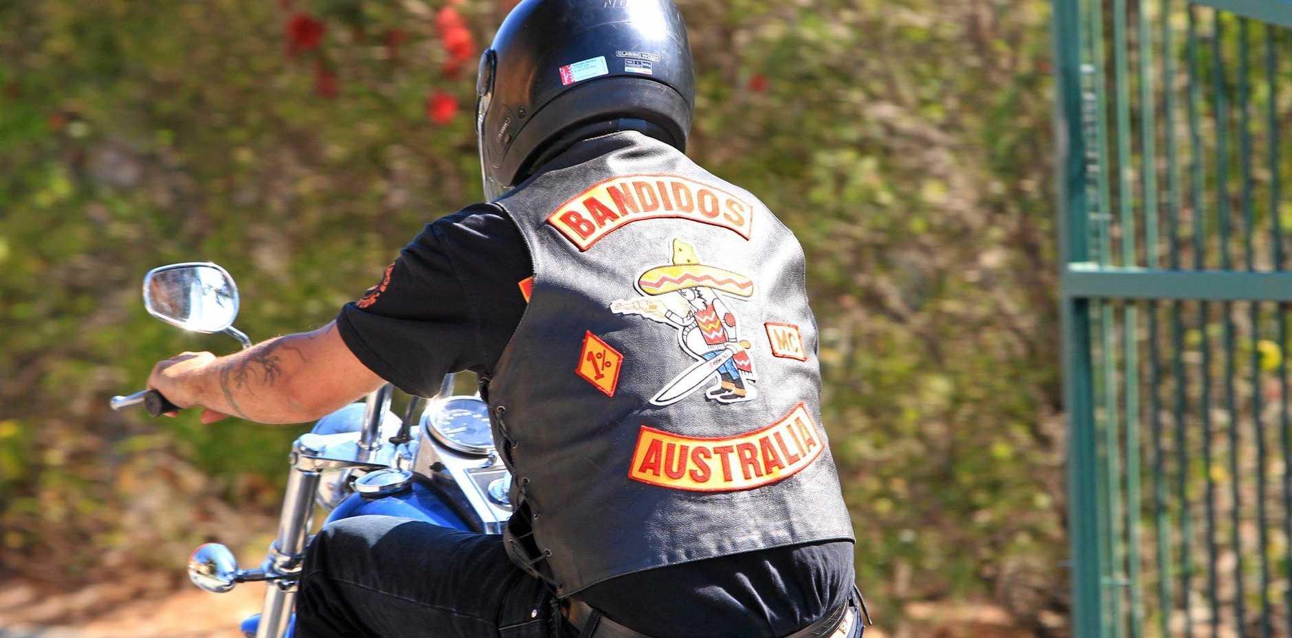 A Bandidos motorcycle club member rides through Caloundra in 2011.