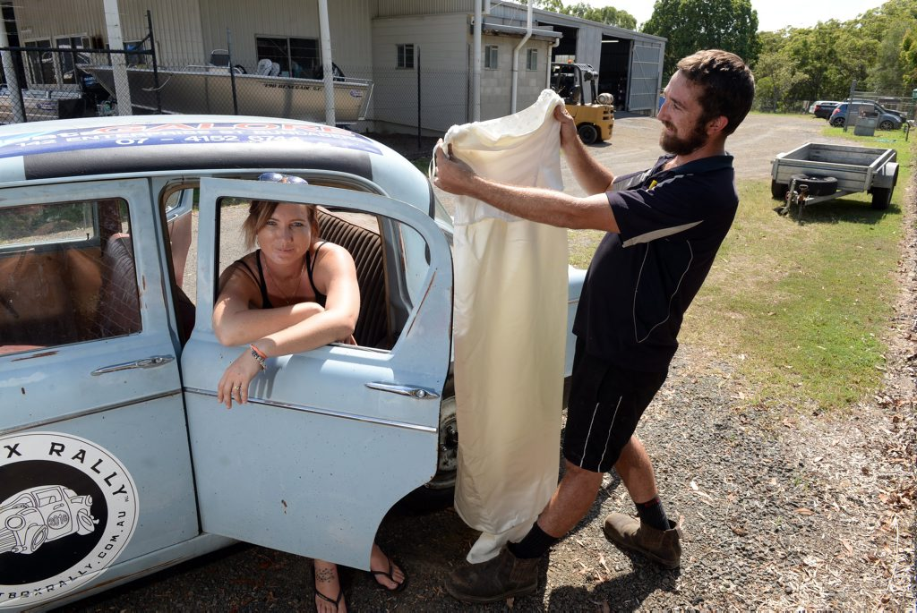 GAME ON: Koryn Turnbull and Matthew Hardgrave with their car that they plan to take on the Shitbox Rally in May. Photo: Max Fleet / NewsMail