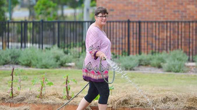 Karen Porter warering the Calliope community garden. Photo Mike Richards / The Observer