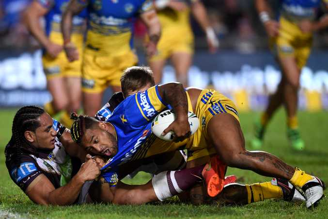 Kenneth Edwards (centre) of the Eels is tackled by Martin Taupau (left) of the Sea Eagles. Photo: AAP Image/Paul Miller