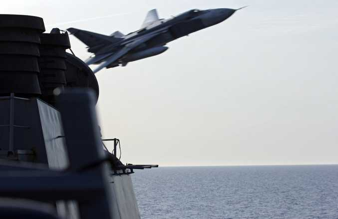 A handout ifrom the US Navy shows a Russian Sukhoi Su-24 attack aircraft making a very low altitude pass by USS Donald Cook (DDG 75) in the Baltic Sea.