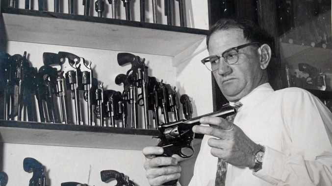 Late police officer Inspector Leslie Bardwell inspects a police pistol at the former Criminal Investigation Branch building in Makerston St, Brisbane in the 1960s.