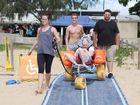 Tony Summerville tries out the Mobi-Mat, assisted by carer Kendrick Lark (right) and Push Mobility's Sian Heaton (left) and James Bean, on Torquay Beach on Sunday. Photo: Jocelyn Watts / Fraser Coast Chronicle
