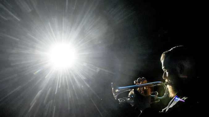 Garrett Salter plays the last post in the spotlight of the Saraton Theatre at the Anzac Commemorative Concert by the Clarence Valley Orchestra and Chorus.
