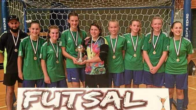 WINNERS ARE GRINNERS: The South-West team of (from l;eft) coach Craig Lockwood, Maddy Lockwood, Izzy Harris, Amy Jocumsen, Lateisha Wilkins, Sarah Holland, Charlotte Crothers, Chloe Hutton and Zoe Doyle celebrate winning the under 12-14 girls Football Queensland Futsal State Championship.