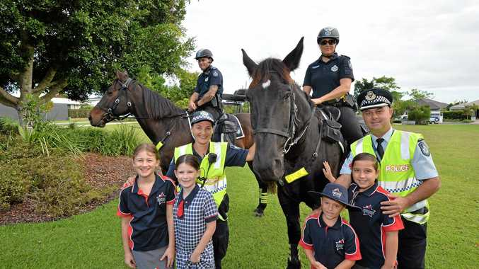 MANE ATTRACTION: (back) Senior Constable Brad Proctor and Senior Constable Kate Blomkamp with police horses Elvis and Hercules. (front) Imogen, 7, and Kirra, 9, Coleman with Senior Constable, (adopt-a-cop) Lynda Dowd, Harley Brian, 6, Payton Faulkner,9, and acting Superintendent, Mike Miley.