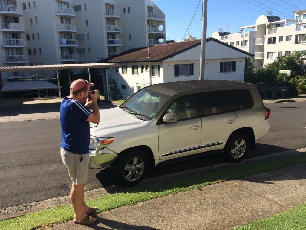 Hotel guest Greg MacMahon takes photos of his soot-covered car after retrieving it from the underground car park at Osprey Apartments in Mooloolaba.