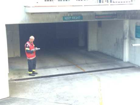 A fire investigator stands at the entrance to the underground car park of Osprey Apartments at Mooloolaba.