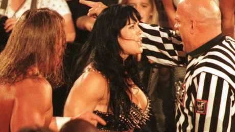 Minnesota Gov. Jesse Ventura, guest referee for the World Wrestling Federation's Triple Threat Championship Match, removes manager Chyna, Joanie Lauer, from ringside as her client Triple H's, Paul Levesque, left, looks on at WWF's SummerSlam held at Target Center in Minneapolis Sunday night, Aug. 22, 1999.