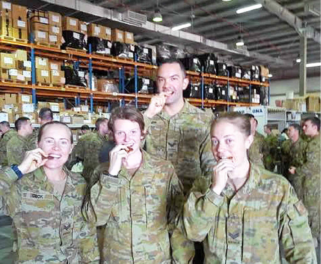 Four Aussie soldiers tuck in to Anzac biscuits.