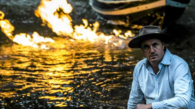 STUNT: Greens MP Jeremy Buckingham set the methane seeps in the Condamine River on fire earlier this month as part of the Greens' campaign to ban fracking and unconventional gas in Australia.