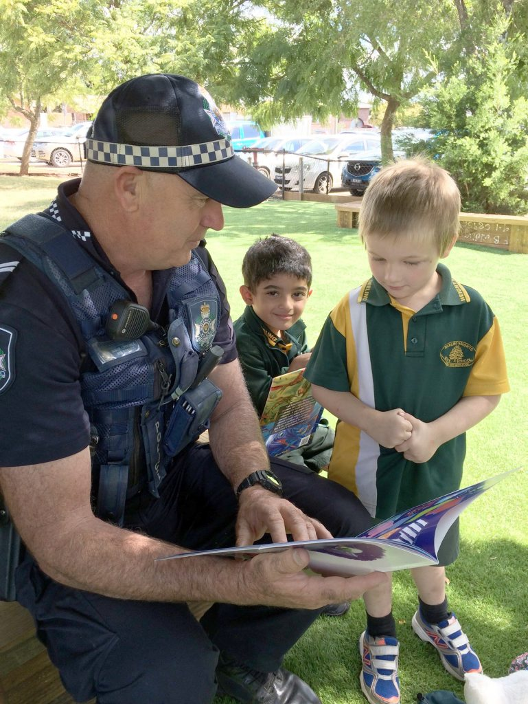 Senior Constable Rob Edwards shares a story with Prep students Ibrahim Allatuf and Jaccob Duffy.