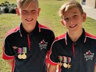 Rex Hobson, 9, (right) with his brother Jack, 11, wearing their grandfather John's medals.