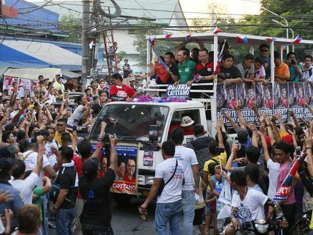 Presidential candidate Mayor Rodrigo Duterte, top left, is greeted by supporters as his campaign motorcade makes its way through the streets of Malabon Wednesday, April 27, 2016 north of Manila, Philippines. The tough-talking Duterte, the mayor of the southern Philippine city of Davao, is the front-running candidate leading to the May 9 presidential elections.