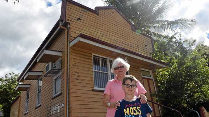Palmwoods woman Anna Stevenson and her grandson Isaak Simpson inspect the front of a former bank which is being considered for state heritage listing.