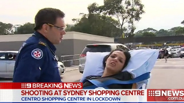 A woman is wheeled away by paramedics after the shooting at Bankstown Central Shopping Centre. Photo: Nine News