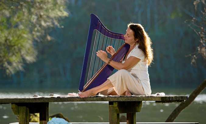 PEACEFUL: Maneeka playing her harp in the serenity of the Woolgoolga Lake Reserve.