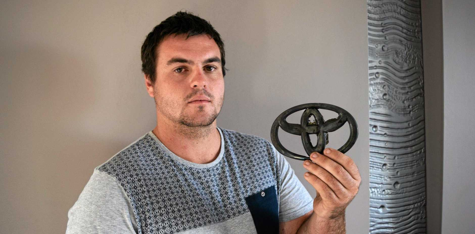 Minyama man Nathan Nicholson holds the charred badge of his Toyota LandCruiser that was stolen and burnt out.