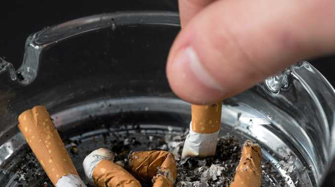 Hand putting out a cigarette in ashtray