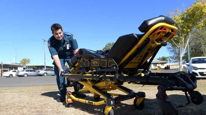 EASIER LIFT: Clinical support officer Cameron Anderson demonstrates the new pneumatic stretcher being introduced to alleviate the problem of back strain amongst paramedics. Photo: Mike Knott / NewsMail