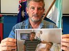 Peter Mitchell holding an image of himself and son, Matthew, who died in an intensive care unit in September 2013 five weeks after being found on Graham Dr, Sandy Beach.