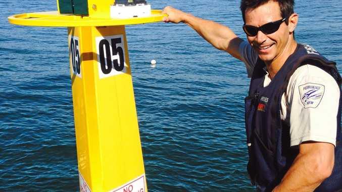 NSW Fisheries officer Glenn Shannon installs the shark listening station off Evans Head.