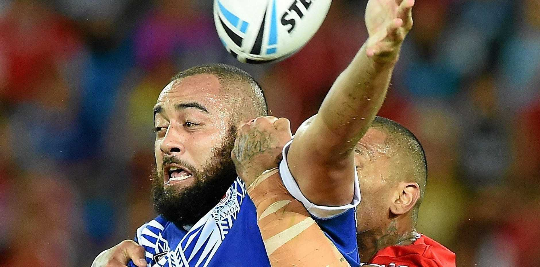 STANDING STRONG: Sam Kasiano offloads the ball in the tackle during the Test match between Samoa and Tonga at Cbus Super Stadium last year.
