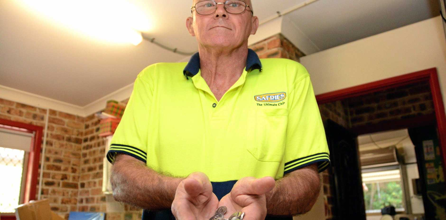 Fingal Trading Post owner Dai Roberts with a handful of the five cent coins that come through his business daily.