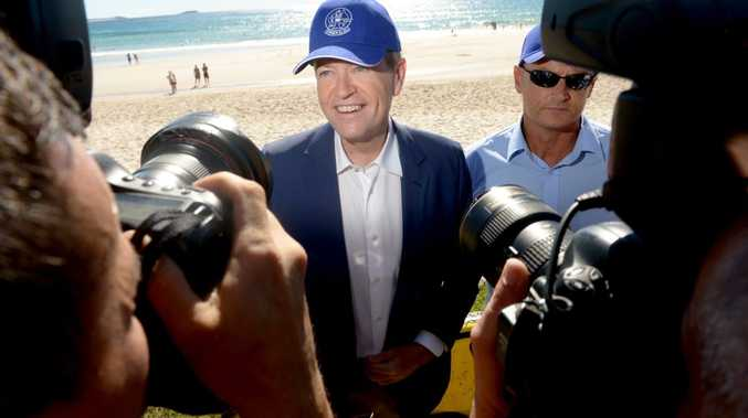 Opposition leader Bill Shorten tries on a hat from Cudgen Surf Life Saving Club in Kingscliff on Sunday, May 15, 2016.