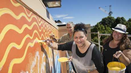 Artist Kim Walmsley (centre) with Tyronne Pearce and Megan Darr work on her project on the side of the Toowoomba Regional Art Gallery as part of First Coat 2016
