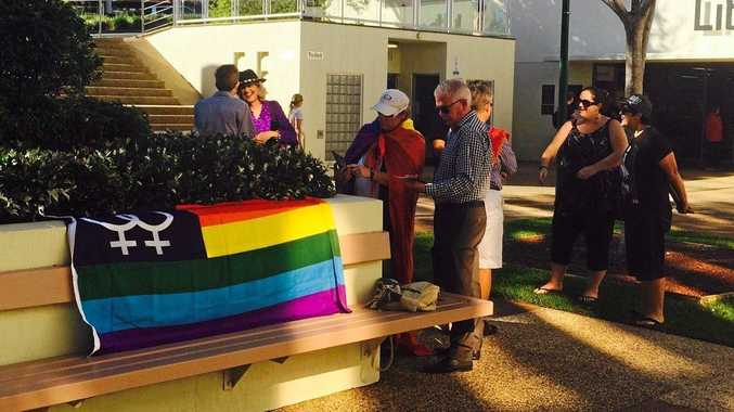 Protesters outside the Sunshine Coast Council chambers at Nambour raise their own rainbow flag.