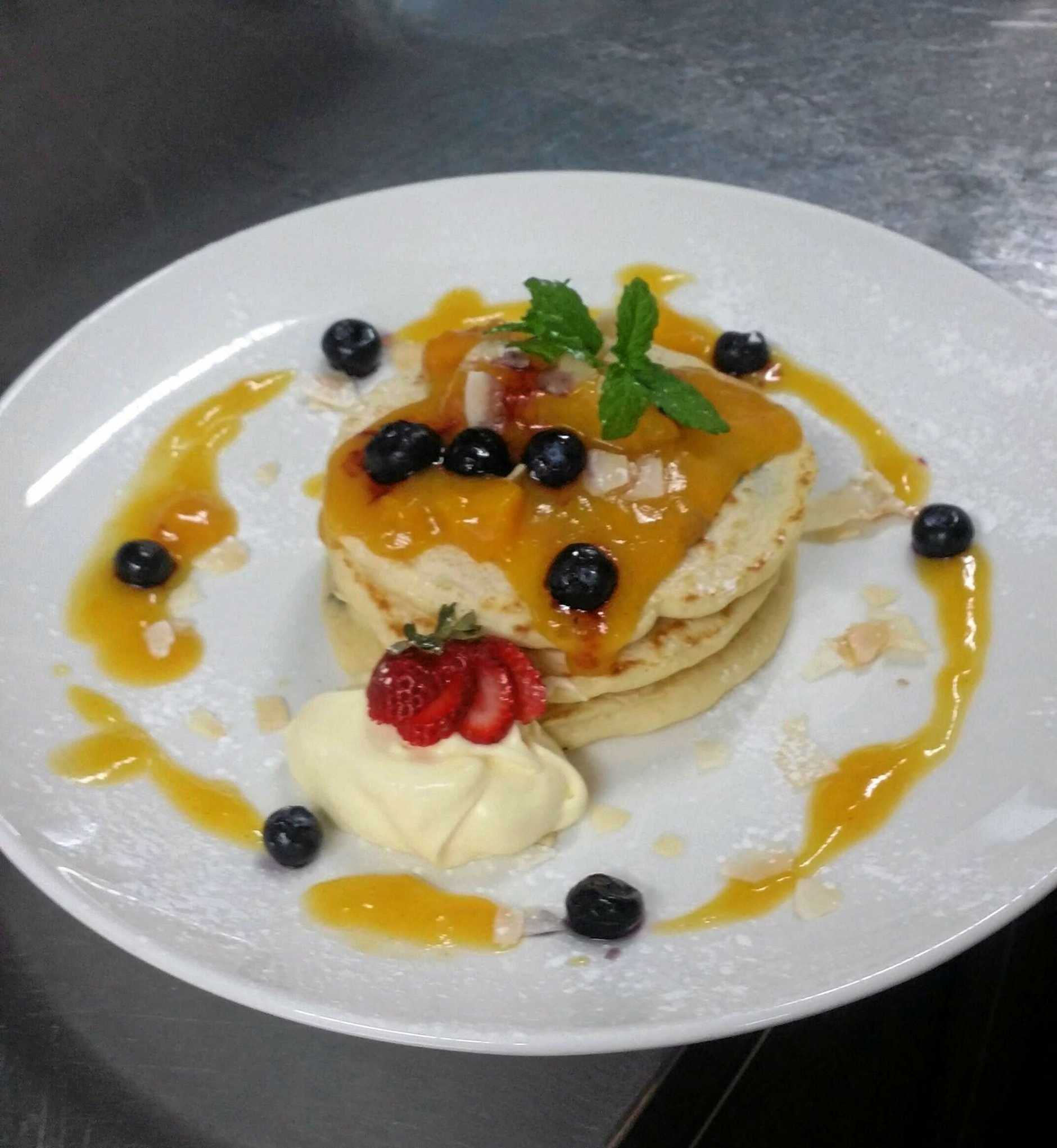 Blueberry pikelets served with  peach syrup, clotted cream and roasted coconut