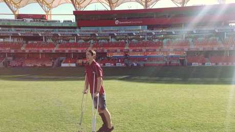 Sunshine Coast Australian rules player Haydyn Cliff makes his way across Metricon Stadium on crutches while recuperating from being hit by a car.