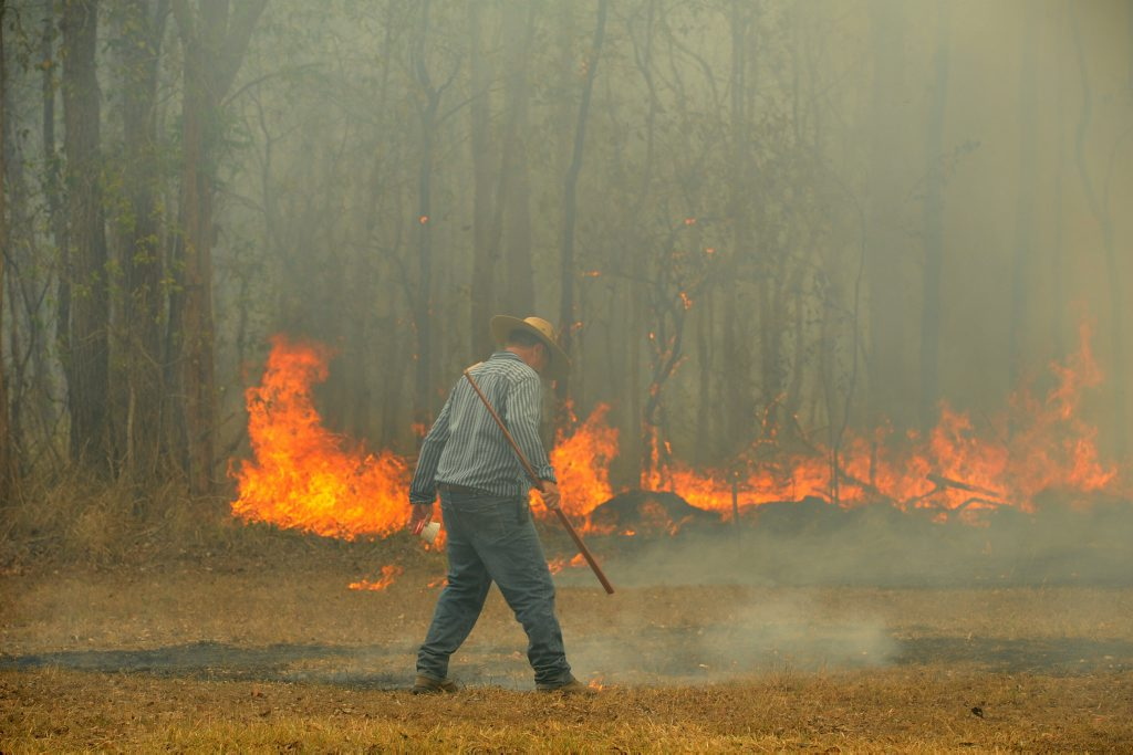 Barry Brunke helps put out a bushfire at the Maryborough Showgrounds on Saturday. Photo: Robyne Cuerel / Fraser Coast Chronicle