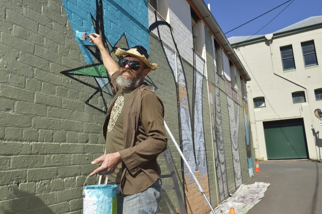Toowoomba artist David Usher paints in Wilcox Ln as part of First Coat 2016, Saturday, May 21, 2016.