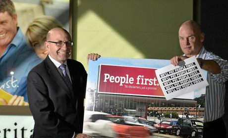 PEOPLE FIRST: Heritage Bank CEO Peter Lock (left) and corporate communications manager Andrew Fox with the ALP campaign sign and bank logo which are causing concern.