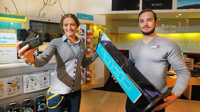 Tweed City Optus staff Charlee Farlow and Michael Anthony, show off phones donated for the muster.