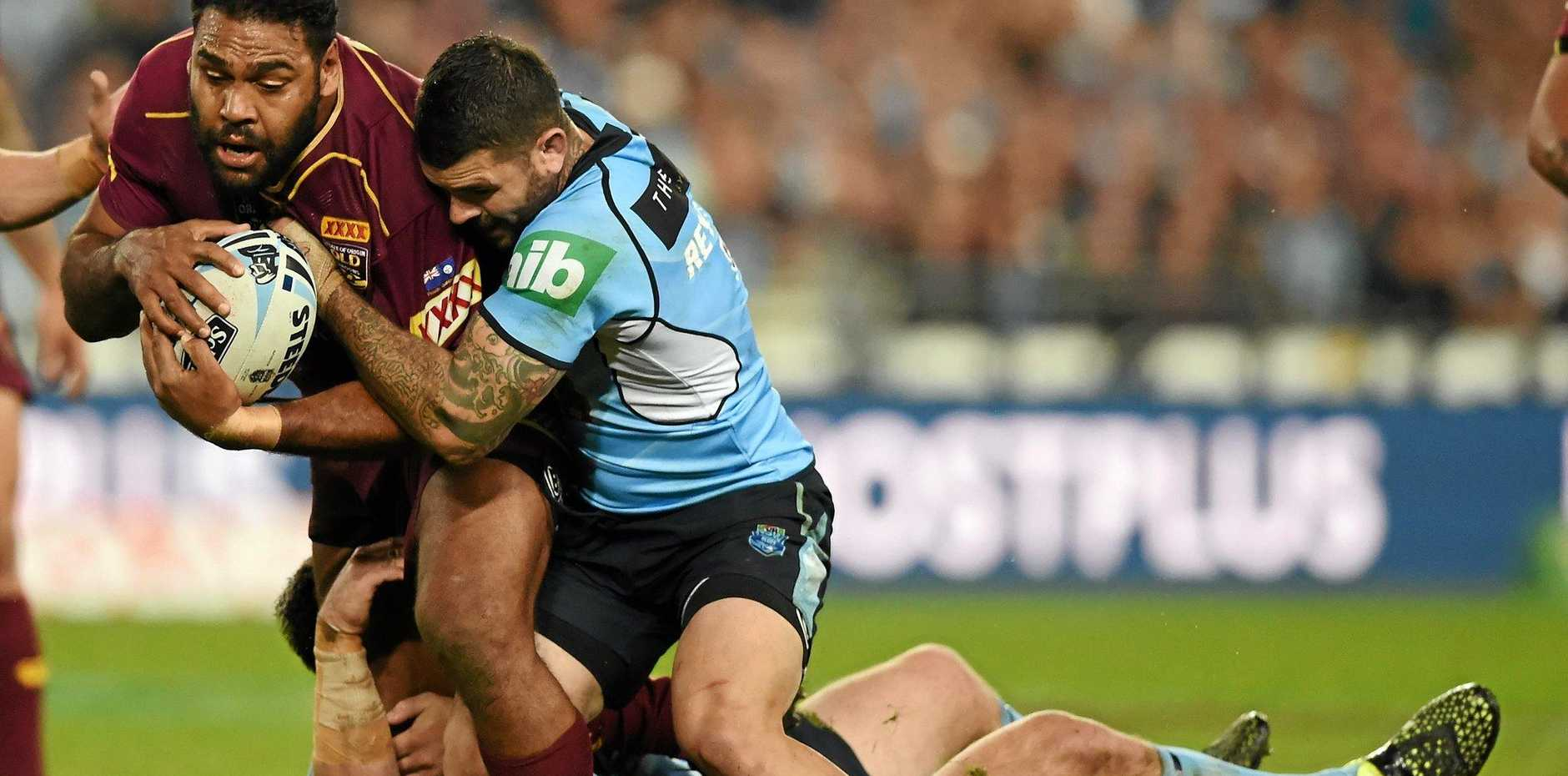 Sam Thaiday is tackled by Adam Reynolds at ANZ Stadium.