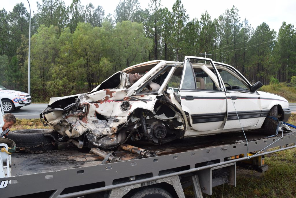A Holden Commodore is loaded onto the back of a tow truck after a crash involving another vehicle on the Bruce Hwy at Beerburrum.