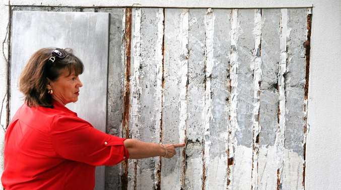 OUR HOME: Resident Janet Hamilton shows a damaged wall within Silverstone units.