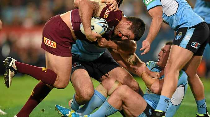 DRIVING FORWARD: Matt Gillett of the Maroons is tackled by Paul Gallen and Aaron Woods of the Blues.