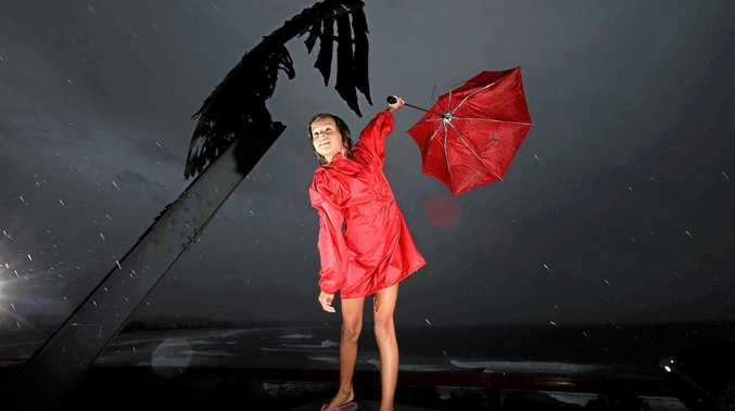 Tweed Heads local Amy Van den Akker struggles to hold her umbrella during the last severe weather event on the Tweed.