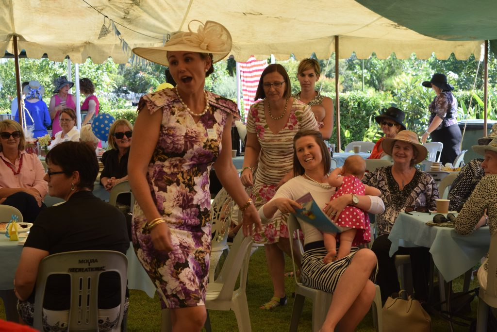 Olivia McDouall (seated) bids for a picnic table as Sarah Morris (left) calls the bid. Photo Andrew Thorpe / Central Telegraph