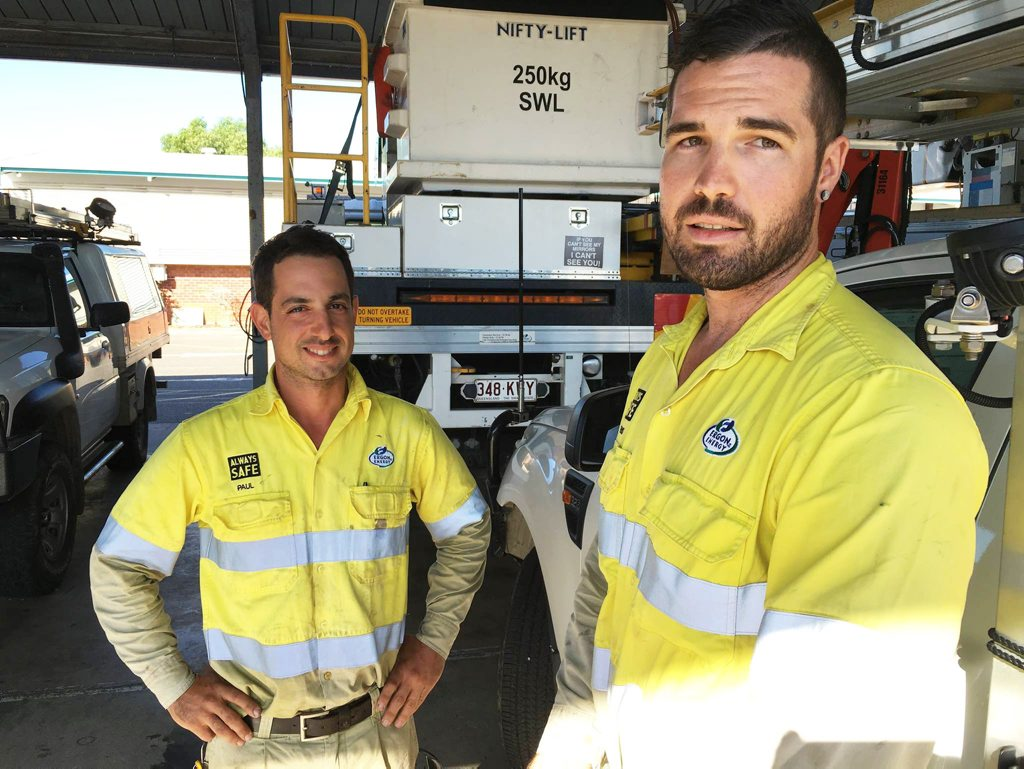 HEROES: Ergon Electrical tradesmen, Paul Sciuto and Trent Stephensen, came to the rescue when a tourist collapsed on a beach in Bowen. Photo contributed/John Fowler