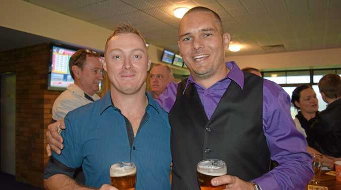 Simon Hindmarsh and Grant McPherson enjoy a beer despite the rain.