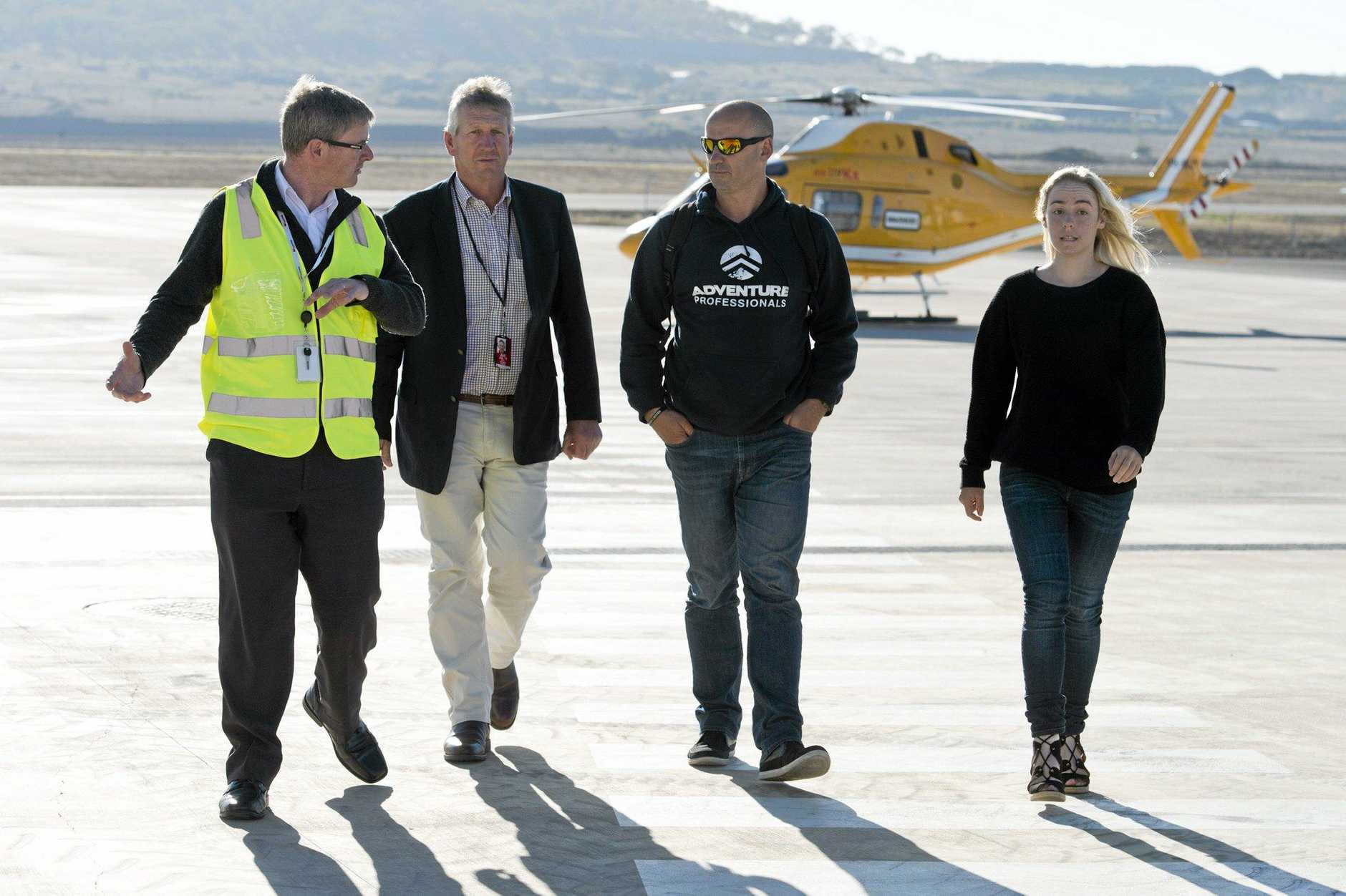 SHE IS HOME: Walking into Wellcamp Airport yesterday are (from left) Wellcamp Airport general manager Phil Gregory and Denis Wagner with Glenn and Alyssa Azar after their arrival by helicopter.