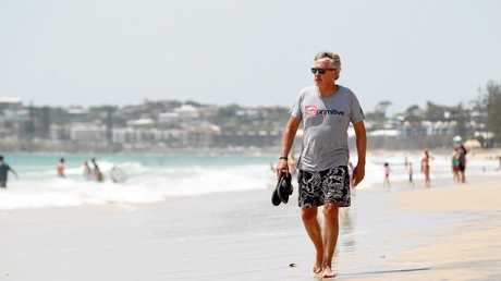 Wayne Swan wets his toes on a scorcher of a day at Maroochydore Beach.