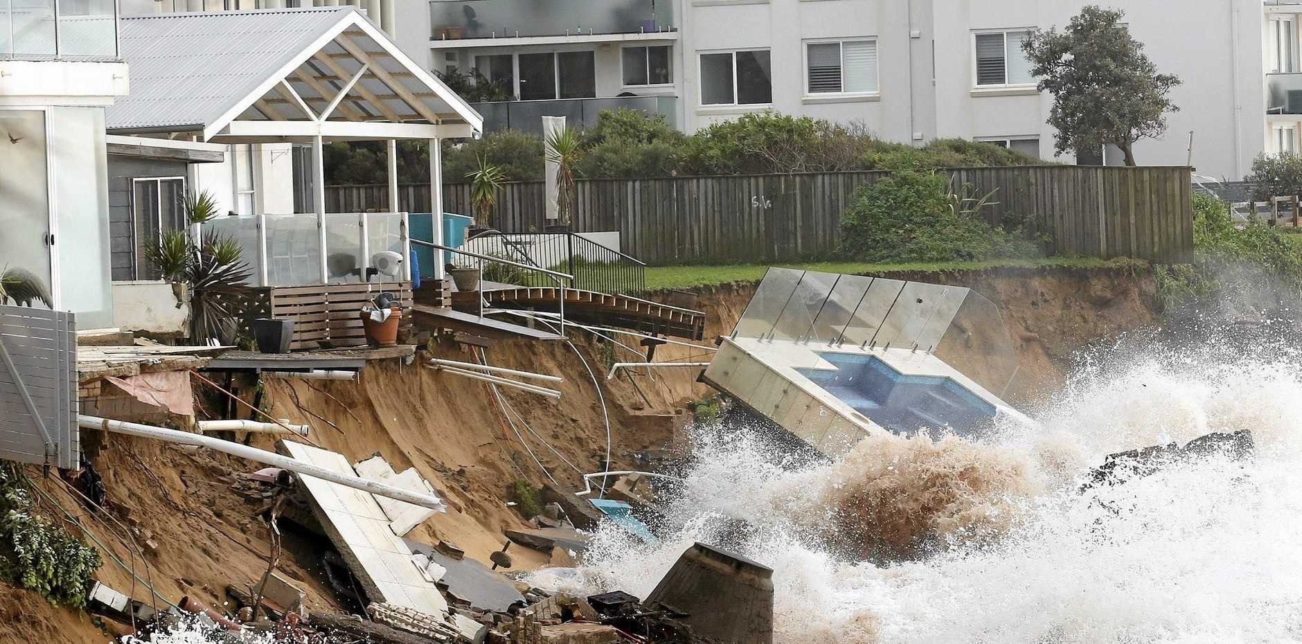 Waves crash against a garden swimming pool that was washed away from a property on the beach front after heavy rain and storms at Collaroy in Sydney's Northern Beaches.