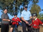 SAFETY FIRST: McDonald's manager Angel Atkinson and Officer-In-Charge of Road Policing Units Mark Woitowitz present Ty Clapperton and Michael MacDonald with free cheeseburger vouchers.